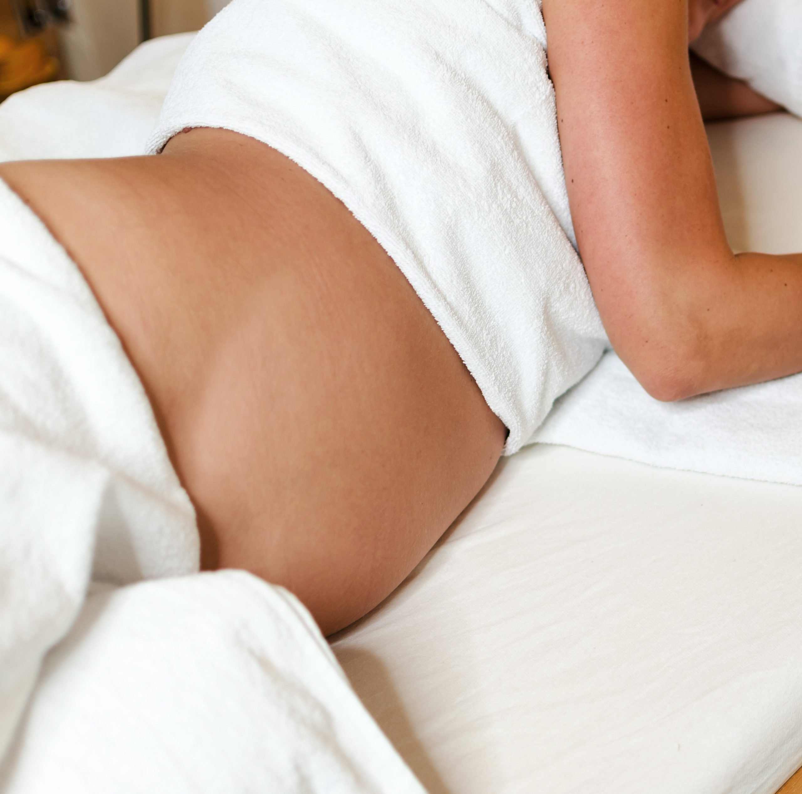 Pregnant Lady getting pregnancy massage and prenatal massage. We come to your home with massage table, linens, candles, music and oil.
